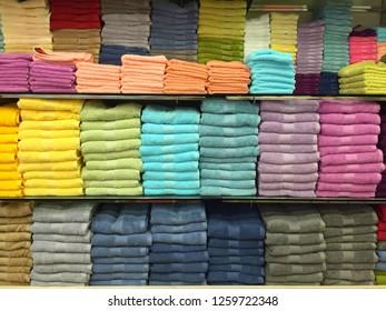Colorful folded towels all arranged neatly on a shelf