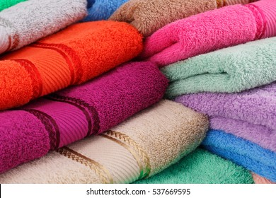 Colorful folded towels stack closeup picture.