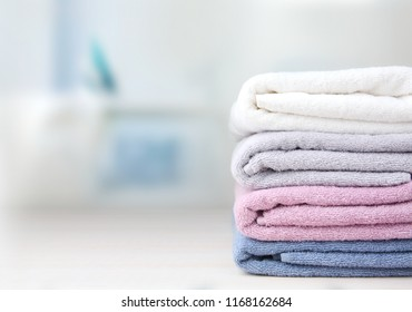Colorful folded towels stack on table empty copy space.