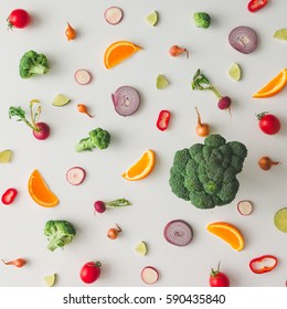 Colorful food pattern made of broccoli, orange, red pepper, onion, tomatoes and lime. Flat lay.