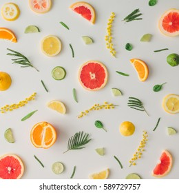 Colorful food pattern made of lemon, orange, grapefruit and flowers. Flat lay.