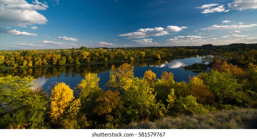 Colorful forest on the banks of large river in autumn