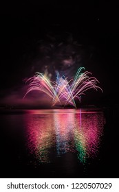 Colorful fountain in fireworks over surface of Brno's Dam with lake reflection