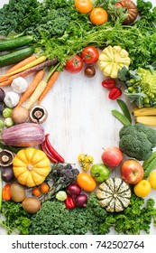 Colorful frame made of fresh raw vegetables, fruits herbs on white wooden background, copy space for text in the middle, top view, selective focus