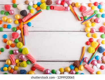 Colorful frame of multicolored candies on white wooden background. Circle copy space, top view, flat lay.