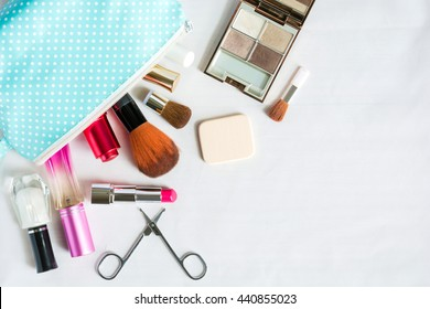 Colorful frame with various makeup products on white background with copy space, bag, lipstick ,powder, perfume, scissors, fingernail paint, brush. The concept cosmetics makeup, beauty, Travel.