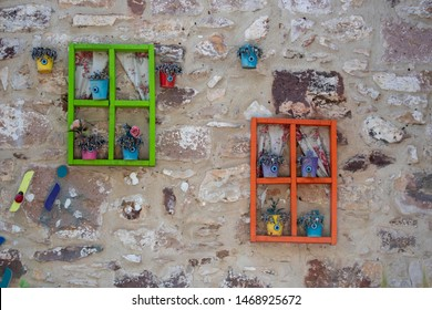 Colorful frames hanging on the wall. Flowerpots placed in the frame. They have evil eye beads.
