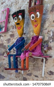 Colorful frames hanging on the wall. Flowerpots placed in the frame. They have evil eye beads.It was taken on the island of Cunda in Ayvalik.Human figures made of broom.