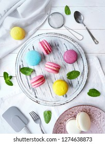 Colorful French dessert macarons stack on white table. Dessert macaroons with kitchen tools and mint leaf