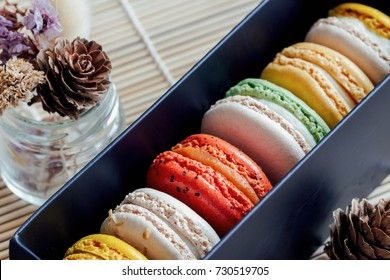 Colorful French or Italian macaron in black gift box in close up view macro concept. Macaron or macaroon is French popular dessert for served with afternoon tea or coffee break. Homemade bakery style.