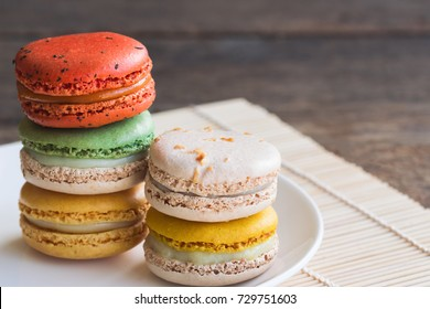 Colorful French or Italian macaron stack on white plate put on wood table with copy space for background. Macarons or macaroons is French dessert for served with afternoon tea or coffee break.