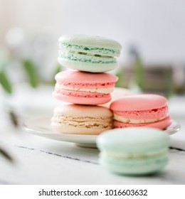 Colorful French or Italian macarons stack on white plate put on wood table with copy space for background. Dessert for served with afternoon tea or coffee break.