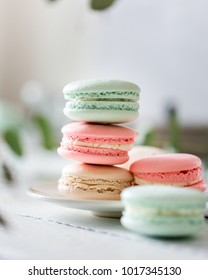 Colorful French or Italian macarons stack on white plate put on wood table with copy space for background. Dessert for served with afternoon tea or coffee break. Beautiful meal background with blank.