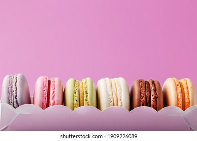 Colorful French macarons cookies in a package on a pink background. Close-up, free space