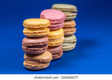 Colorful french macarons isolated on blue background. Pastel colors - Imagen