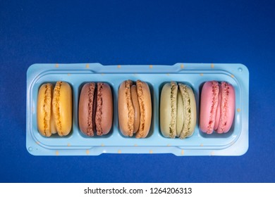 Colorful french macarons isolated on blue background placed in your sale stand. Pastel colors - Image
