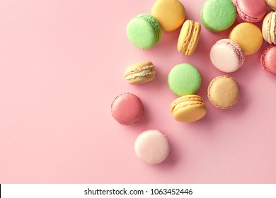 Colorful french macarons on pink background. Top view. Pastel colors