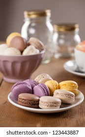 Colorful French macarons served on a rustic wooden table, on a white plate.