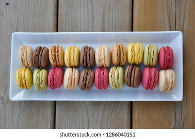 Colorful french macarons in a white rectangular plate over the wooden table