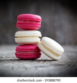 Colorful French macaroons and cup of tea on a dark rustic wooden background, selective focus
