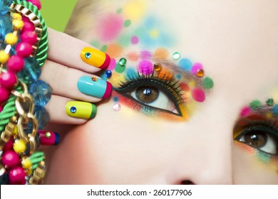 Colorful French manicure and makeup on the girl with rhinestones.