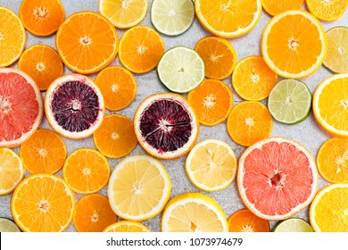 Colorful fresh cut citrus fruit background with a large assortment of halved different fruits showing the juicy pulp in a full frame view