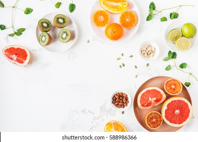 Colorful fresh fruit on white table. Orange, tangerine, lime, kiwi, grapefruit. Summer fruit. Flat lay, top view, copy space