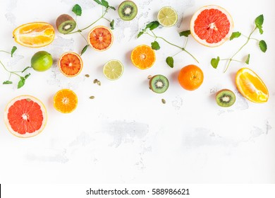 Colorful fresh fruit on white table. Orange, tangerine, lime, kiwi, grapefruit. Fruit background. Summer food concept. Flat lay, top view, copy space.