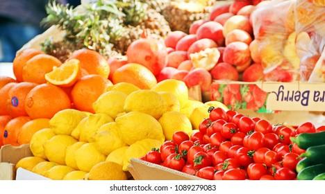 Colorful fresh fruits and vegetable such as orange, lemon, cucumber, apple, tomato etc. in flea market.