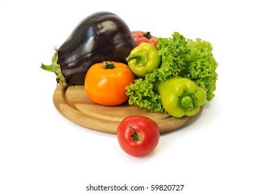 Colorful fresh group of vegetables on a wooden board. White background