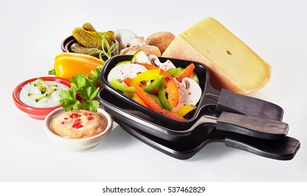 Colorful fresh ingredients for making raclette for dinner with a large wedge of Swiss cheese, diced vegetables, sauces or dips, potatoes, herbs and pickles with a stack of small skillets