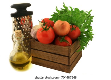 Colorful fresh ingredients, seasoning and tool for cooking tomato souse. Organic tomatoes, garlic, onion, plain parsley in wooden crate, olive oil, handhold kitchen shredder over white background