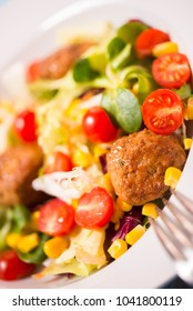 Colorful fresh vegetable salad with meatballs and corn seeds on rustic background. Close-up photo, selected focus. Copy space