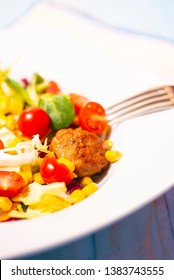 Colorful fresh vegetable salad with meatballs on rustic background. Copy space.