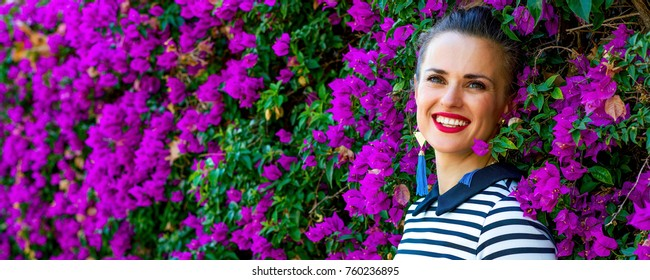 Colorful Freshness. Portrait of relaxed young woman in  stripy shirt in the front of colorful magenta flowers bed