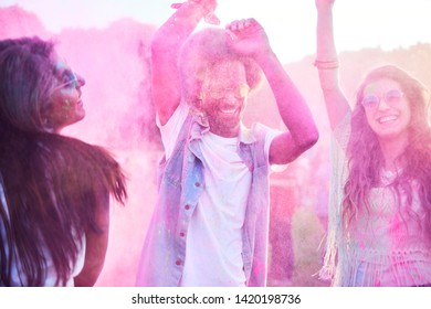 Colorful friends dancing in holi colors
