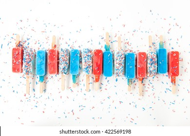 Colorful frozen popsicles in red,white and blue with sprinkles