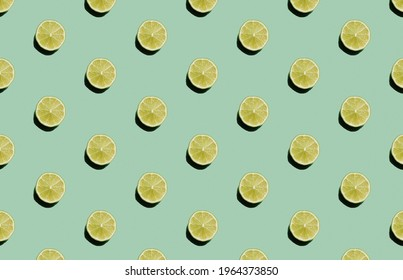 Colorful fruit diagonal pattern on green background. Fresh lime slices. Minimalistic food concept