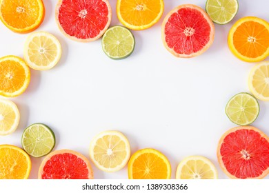 Colorful fruit frame of fresh citrus slices. Top view, flay lay over a white background with copy space.