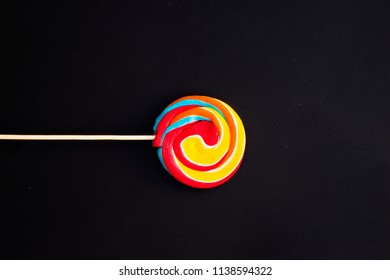colorful fruit lollipops on a black background, unhealthy but delicious snack for children,