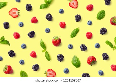 Colorful fruit pattern of berries and mint leaves on yellow background. Top view. Flat lay