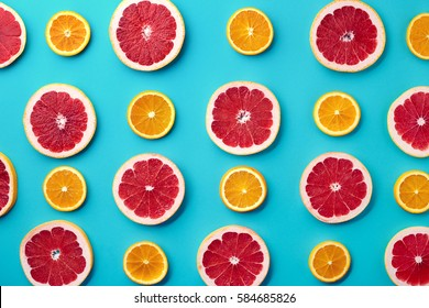 Colorful fruit pattern of fresh orange and grapefruit slices on blue background. From top view