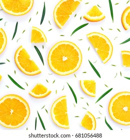 Colorful fruit pattern of fresh orange slices and small green leaves on white background. From top view