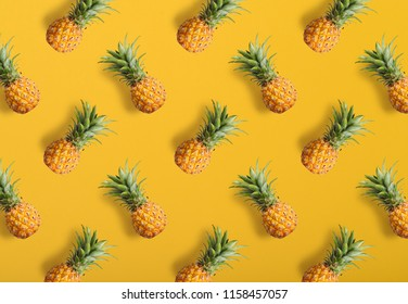 Colorful fruit pattern of fresh pineapples on yellow background, top view