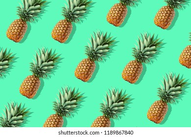 Colorful fruit pattern of fresh whole pineapples on green background
