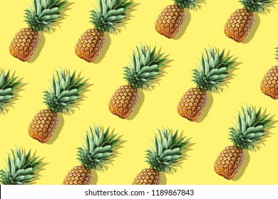 Colorful fruit pattern of fresh whole pineapples on yellow background