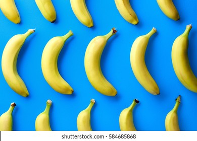 Colorful fruit pattern of fresh yellow bananas on blue background. From top view