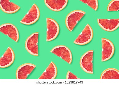 Colorful fruit pattern of grapefruit slices on green background. Top view. Flat lay