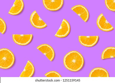Colorful fruit pattern of orange slices on purple background. Top view. Flat lay