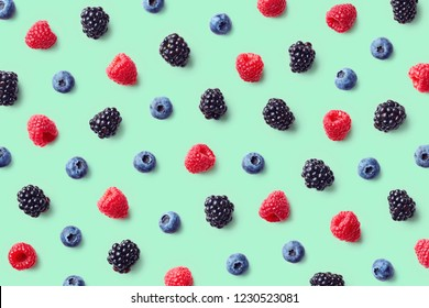 Colorful fruit pattern of wild berries on blue background. Raspberries, blueberries and blackberries. Top view. Flat lay